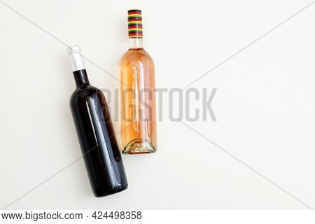 Rose Wine Bottle And Red Wine Bottle . Minimalistic Wine Composition Top View On White Background. T