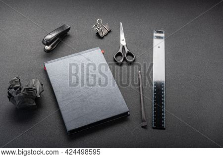 Black Office Supplies On A Black Table. Black Ruler And Black Notebook.
