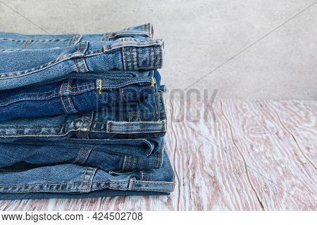 Jeans Trousers Stack On Wooden Board With Copy Space, Concept Jean In Supermarket