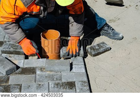 Construction Of A Sidewalk Near The House. The Bricklayer Lays Concrete Paving Stones For The Device
