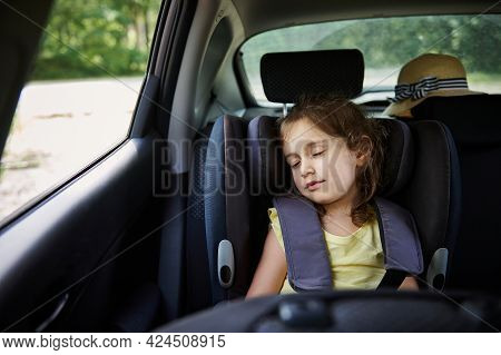 Little Girl Sleeps In A Booster Seat In The Car. Child Safety Seat.. Safe Movement Of Children In Th