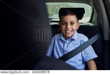 Shot Through The Driver Seat Of A Smiling School Boy Fastened With Seatbelt While Travelling By Car