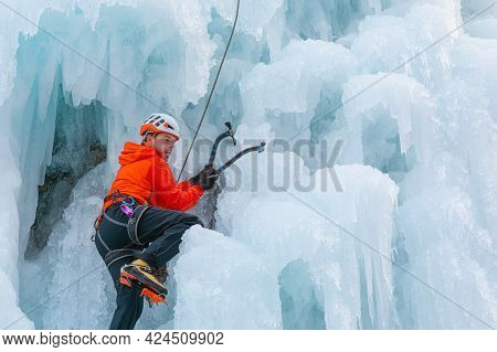 Athlete Climb Frozen Waterfall, Swinging The Axe Pick Into The Ice And Using It As A Grip To Pull Hi