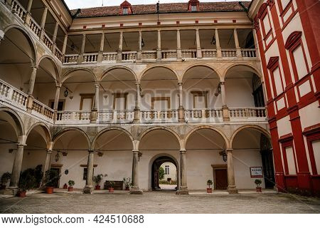 Opocno Castle, Renaissance Chateau, Courtyard With Arcades And Red Facade, Palm Trees And Plants In