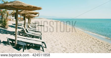 some sun umbrellas made with natural materials and some beige sunloungers, on a quiet beach, in a panoramic format to use as web banner or header