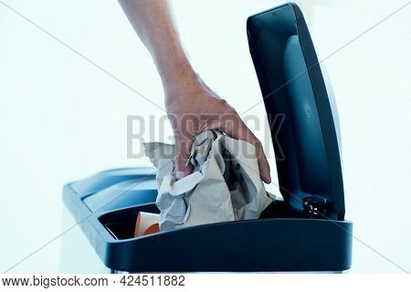 a young caucasian man throws a ball of paper in the paper and cardboard compartment of a home recycling bin