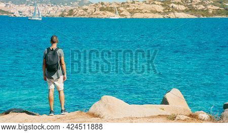 young man, carrying a backpack, observes the coast of the Mediterranean sea in Sardinia, Italy, looking towards La Maddalena and Santo Stefano islands, in the Strait of Bonifacio, in the background