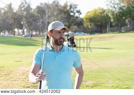 Male Golf Player On Professional Golf Course. Portrait Of Golfer In Cap With Golf Club.