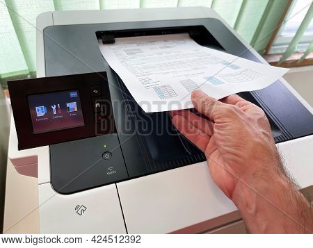 Hand Holding A Sheet Of Paper With A Freshly Printed Report On A Modern Wifi Multifunction Printer W