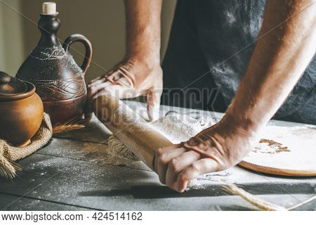 Male Hands Roll Dough And Flour With Rolling Pin Next To Clay Pot And Oil Bottle On Dark Table While