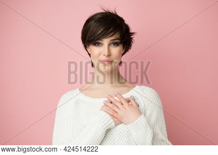 Young pretty woman smiling and looking at camera with hands on chest and grateful gesture on her face. Happy woman feels grateful, hope, believes in success, wishes dream come true, visualizes future.