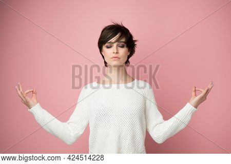Young pretty woman meditate over pink background. Relaxation, piritual practice and yoga