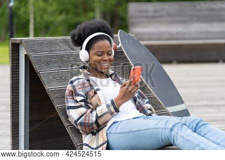 Cheerful Black Female With Skateboard Chat On Smartphone With Smile Sit In Skate Urban Park Use Phon