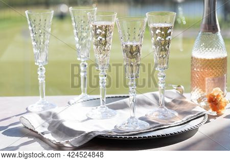 Crystal Flute Wine Glasses With Three Of Them Having Some Sparkling Rose Wine In Them, Against A Sun