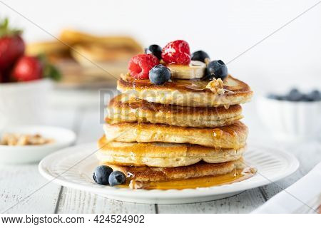 Close Up Of A Stack Of Buttermilk Pancakes Topped With Berries And Syrup Dripping Down The Sides.