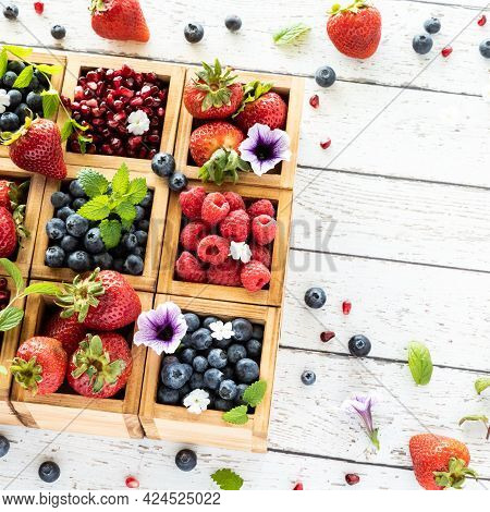 Top Down View Of Crates Of Berries On A Rustic Wooden Table With Copy Space To The Right.