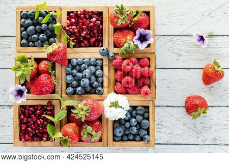 Various Berries In Wooden Boxes On A Rustic Wooden Table With Copy Space To The Right.