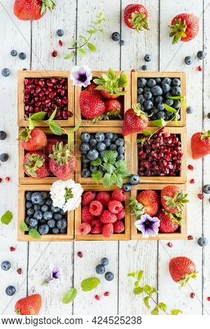 Top Down Vertical View Of A Compartment Box Filled With Different Types Of Berries And Berries Scatt
