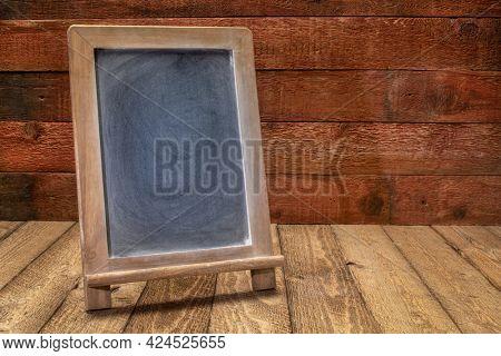 blank blackboard sign on a rustic weathered wood