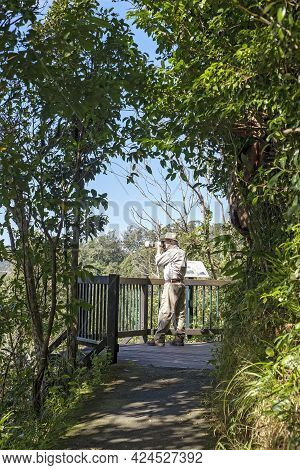 Mackay, Queensland, Australia - June 2021: An Active Senior Pensioner Photographing The Scenery From