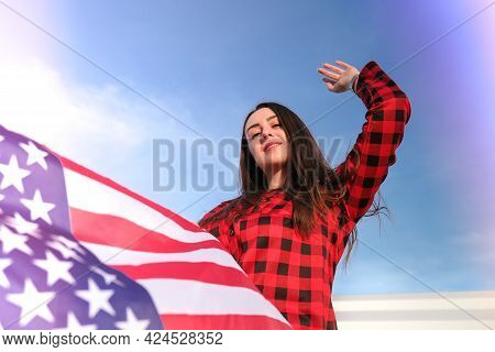 Young Millennial Brunette Woman Holding The National Flag Of Usa. American Flag. Tourist Traveler Or