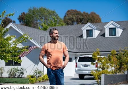 Portrait Of Young Handsome Man Real Estate Agent Standing Near New House. Estate Agent And House.