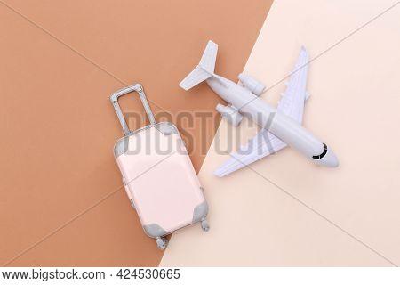Travel Minimalism. Mini Plastic Travel Suitcase And Air Plane On Beige Brown Background. Minimal Sty