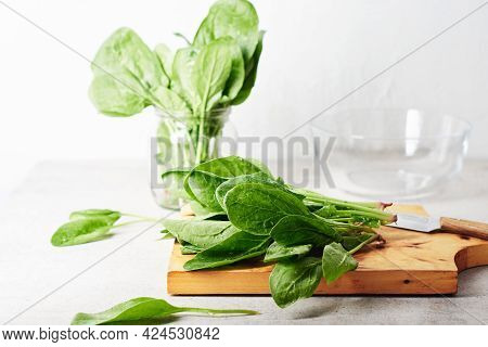 Fresh Green Spinach Leaves On A Kitchen Board.