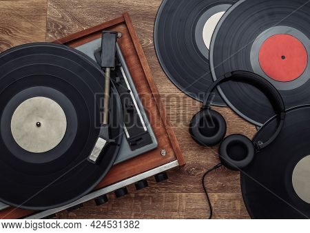 Retro Vinyl Player And Stereo Headphones On Wooden Background. Top View. Flat Lay