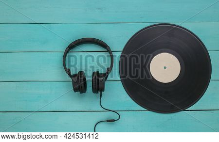Retro Vinyl Record And Stereo Headphones On Blue Wooden Background. Top View. Flat Lay