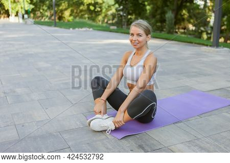 Cheerful Smiling Fitness Woman Practicing Hatha Yoga While Sitting On Mat Outdoors