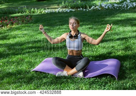 Young Fitness Woman Meditates While Sitting On The Mat In The Park. Lotus Position, Yoga Hatha