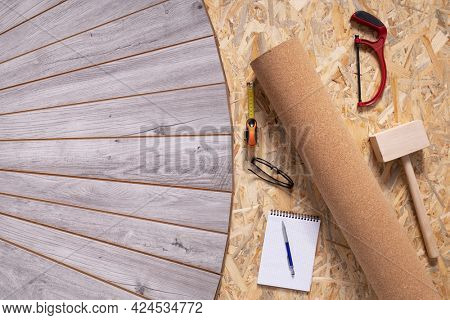 Laminate floor and tools as wood background texture. Wooden laminate floor plank with copy space