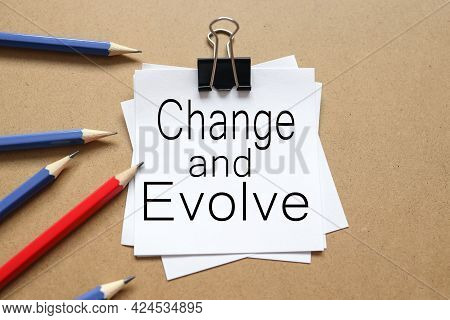 Change And Evolve. Text On The Sticker. Paper Is Clamped With A Paper Clip. Paper On A Wooden Backgr