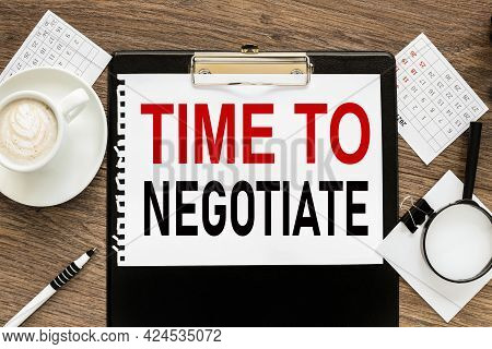 Time To Negotiate . Text On Wood Table, On White Paper