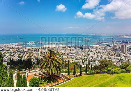 Israel. View from Mount Carmel to the international seaport of Haifa. Clear sunny day. Gorgeous colorful gardens, flower beds, cypress trees and green lawns attract pilgrims and tourists.