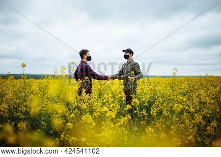 Two Farmers Or Agronomists In Black Protective Masks Stand In A Ripe Rapeseed Field Shaking Hands. C