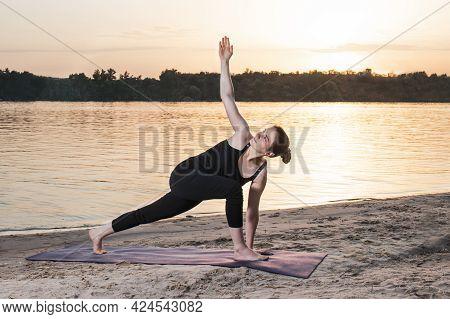 Girl Doing Yoga - Extended Side Angle Pose Utthita Parsva Konasana. On A Mat On The Beach By The Riv