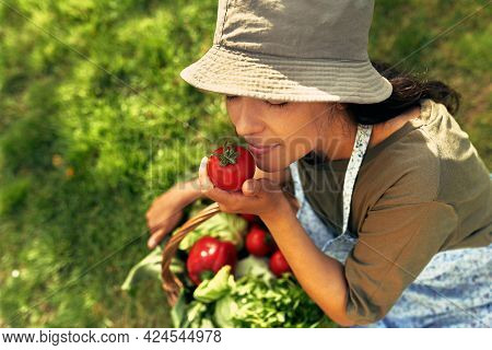 Closeup Of A Happy Female Gardener With A Basket With Freshly Picked Ecological Vegetables At The Fa