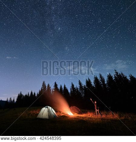Man Hiker Near Campfire And Pointing Finger At Night Sky With Stars. Picturesque View Of Blue Starry