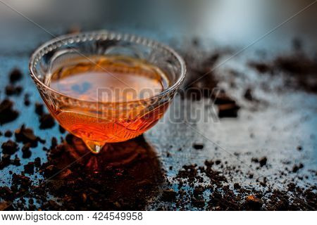 Close-up Shot Of Honey In A Glass Bowl On The Black Surface Along With Some Raw Cocoa Powder Sprinkl