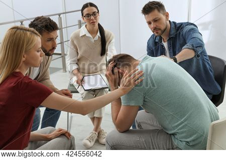 Psychotherapist Working With Group Of Drug Addicted People At Therapy Session Indoors