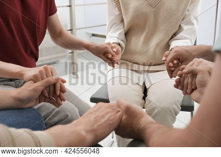 Psychotherapist And Group Of Drug Addicted People Holding Hands Together At Therapy Session, Closeup