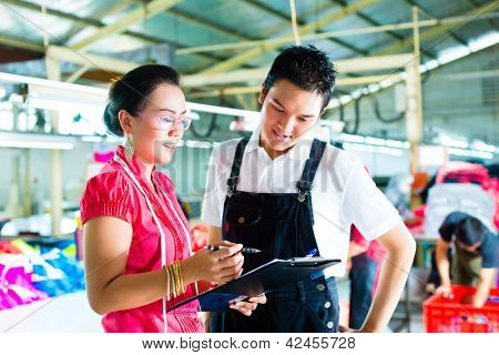 Worker or foreman and dressmaker or designer looking on Clipboard in a factory