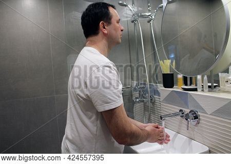 A Man Washes His Hands With Water In The Bathroom Sink. The Concept Of An Attentive Attitude To Clea