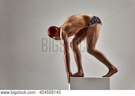 Swimmer Man Preparing To Jump, Young Athlete, Swimmer On A Gray Background, Swimming Healthy Lifesty