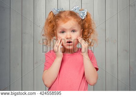 Scared Timid Redhead Little Girl In Casual Pink T Shirt, Looking Frightened And Anxious, Feeling Ner