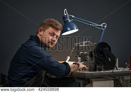 A Tanner Or Skinner Sews Leather On A Special Sewing Machine, Side Shot, Blue Background, A Worker S