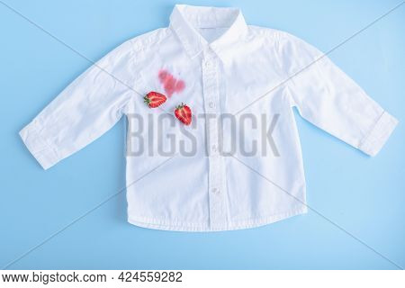 Dirty Stain Of Strawberry On A White Shirt. Daily Life Dirty Stain. Isolated On A Blue Background