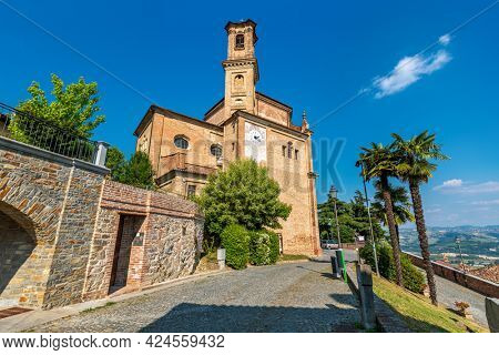 Narrow cobblestone street and old brick church under blue sky in small town of Guarene in Piedmont, Northern Italy.